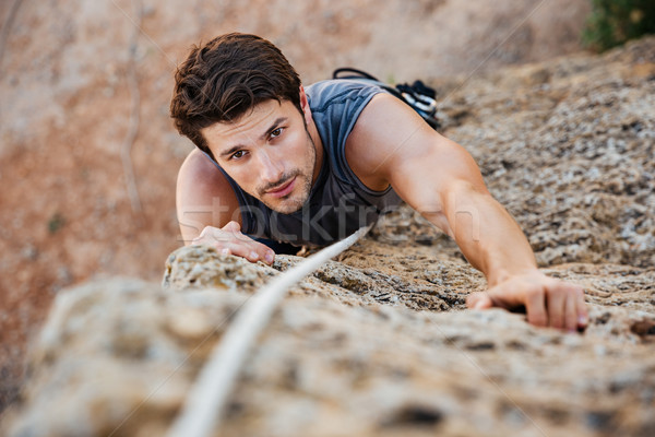 Man reaching for a grip while he rock climbs Stock photo © deandrobot