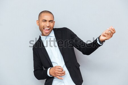 Attractive man taking his jacket off over gray background Stock photo © deandrobot