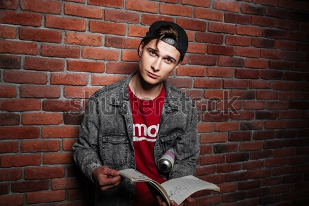 Graffiti man holding sketchbook isolated over red brick wall Stock photo © deandrobot