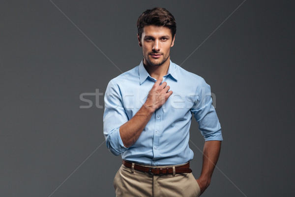Handsome serious man buttoning his shirt isolated Stock photo © deandrobot