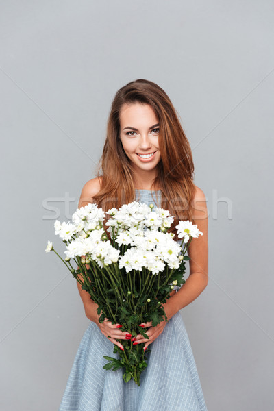 Happy beautiful young woman holding bouquet of flowers Stock photo © deandrobot