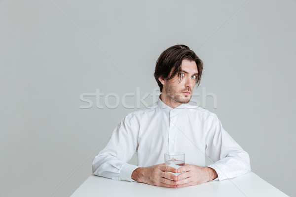 Man with eyes wide open sitting and holding water glass Stock photo © deandrobot