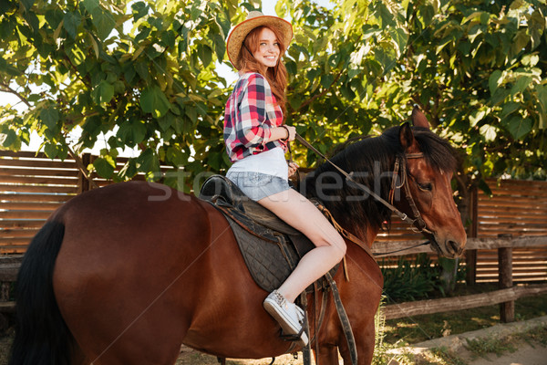 Cheerful woman cowgirl riding horse on ranch Stock photo © deandrobot