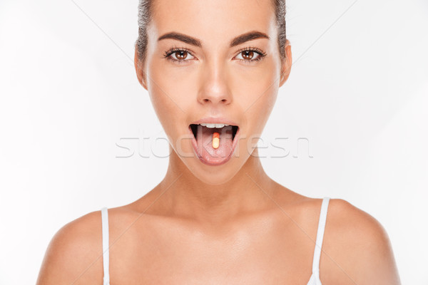 Portrait of a pretty girl with vitamin capsule on tongue Stock photo © deandrobot