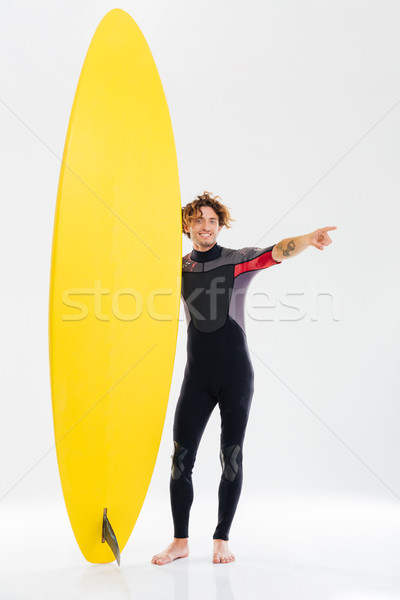 Cheerful young surfer holding surfboard and pointing finger away Stock photo © deandrobot