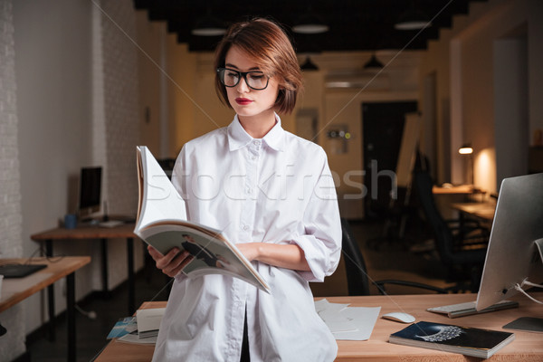 Beautiful young businesswoman standing and reading magazine in office Stock photo © deandrobot