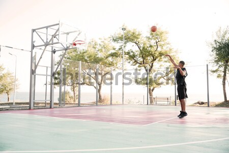 Young african basketball player looking at hoop Stock photo © deandrobot
