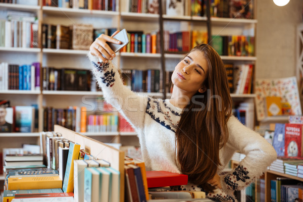 Pretty young woman taking selfie with mobile phone in library Stock photo © deandrobot