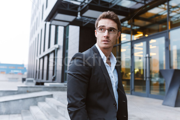 Young Business man in glasses near the office Stock photo © deandrobot