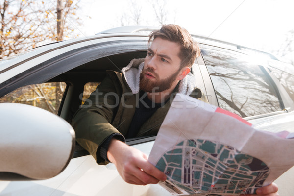 Losted in forest driver holding map and looking aside. Stock photo © deandrobot