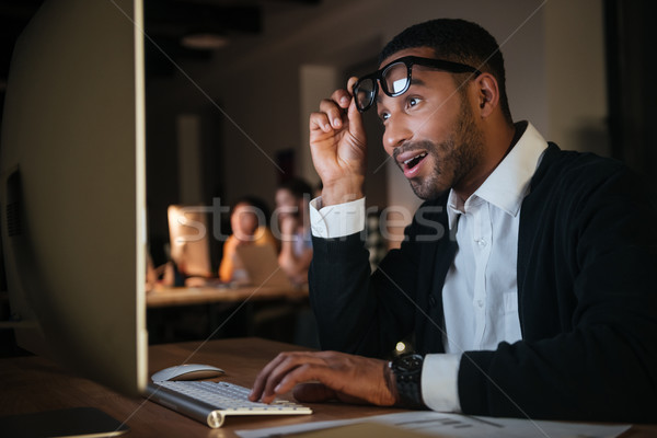 Shocked businessman working at night in office with computer Stock photo © deandrobot
