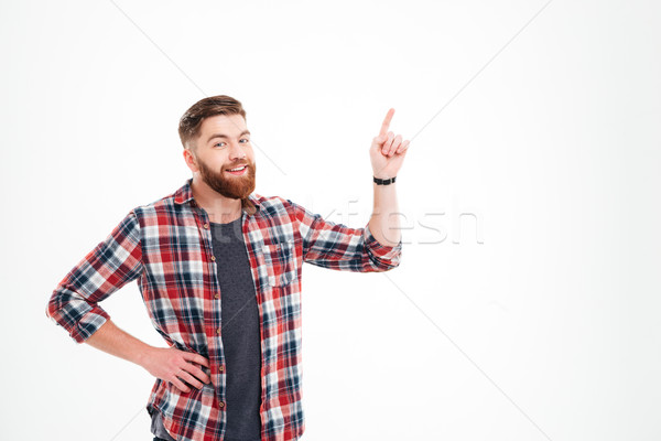 Smiling man in plaid shirt pointing finger up at copyspace Stock photo © deandrobot