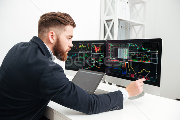 Serious businessman working with computer and making graphs in office Stock photo © deandrobot