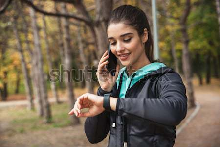 Lady runner in warm clothes and earphones in autumn park Stock photo © deandrobot