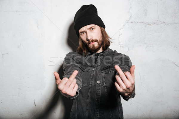 Portrait of a man in hat showing fuck you sign Stock photo © deandrobot