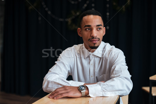 Businessman sitting near table and look aside Stock photo © deandrobot