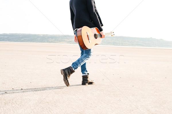 Casual man holding guitar and walking across seashore Stock photo © deandrobot