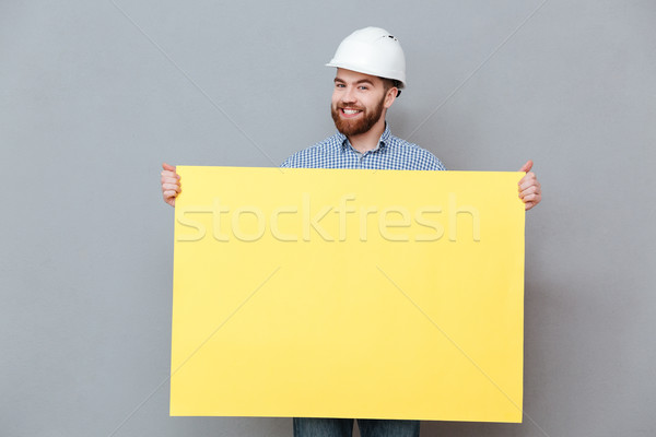 Happy young bearded builder holding copyspace board Stock photo © deandrobot