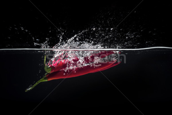 Red hot chili pepper splashing into water Stock photo © deandrobot