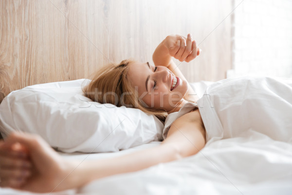 Side view of woman waking up after sleep Stock photo © deandrobot