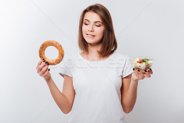 Hungry young lady holding bagel and salad Stock photo © deandrobot