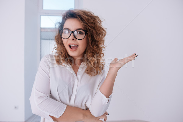Surprised Woman in shirt and glasses with open mouth Stock photo © deandrobot
