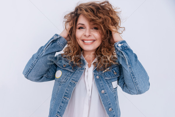Woman in jean jacket straightens hair Stock photo © deandrobot