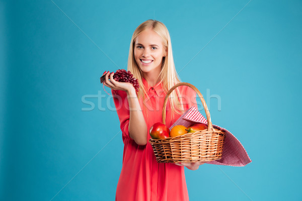 Smiling young woman holding straw basket with healthy food fruits Stock photo © deandrobot