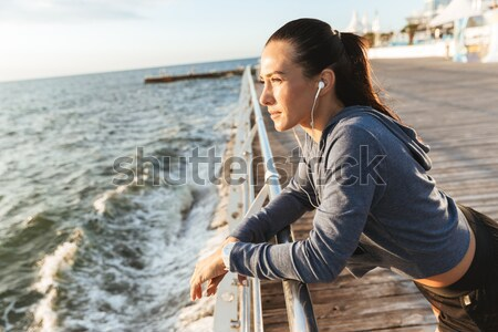 African man wearing hat and scarf sitting on a bench Stock photo © deandrobot