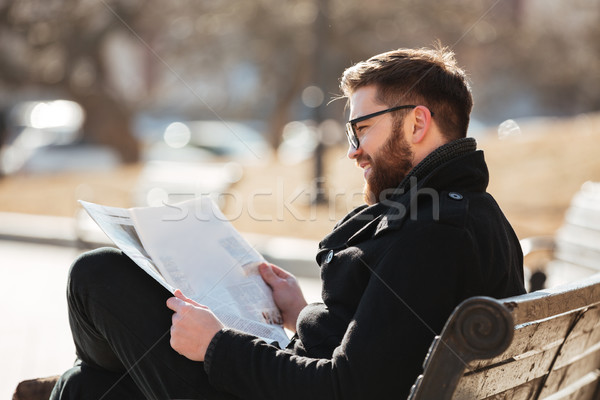 Stock photo: Smiling man in glasses reading newspaper on the bench outdoors
