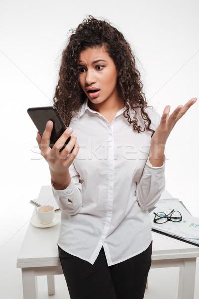 Amazed astonished african young businesswoman standing and using cell phone Stock photo © deandrobot
