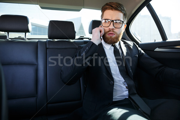 Confident young businessman talking on mobile phone Stock photo © deandrobot