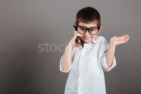 Confused little boy talking on cell phone and holding copyspace Stock photo © deandrobot
