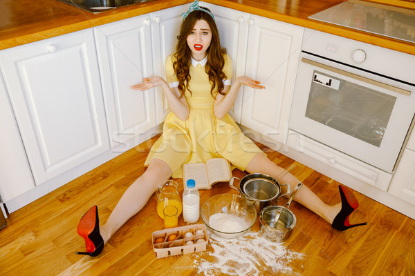 Confused young pin-up woman sitting on floor and cooking. Stock photo © deandrobot