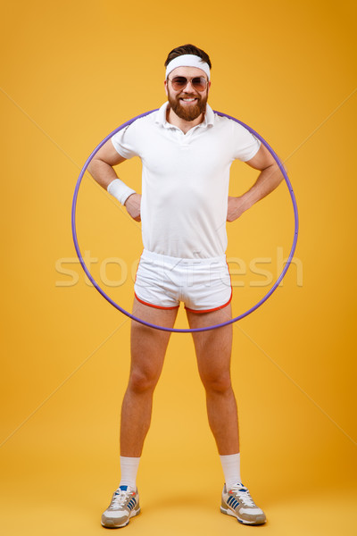 Smiling young sportsman wearing glasses with gymnastic hoop Stock photo © deandrobot