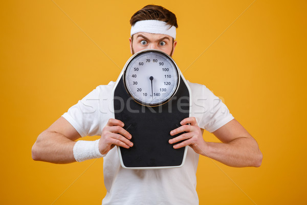 Portrait of a young fitness man hiding behind weight scales Stock photo © deandrobot