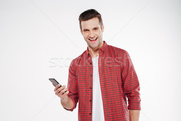 Smiling man holding smartphone Stock photo © deandrobot