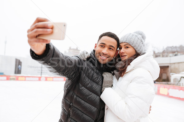 Happy loving couple skating at ice rink outdoors. Make selfie. Stock photo © deandrobot