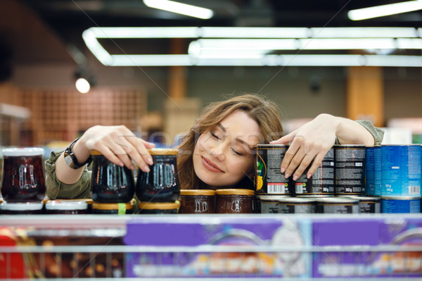 Young woman sleeping on groceries on a supermarket aisle Stock photo © deandrobot