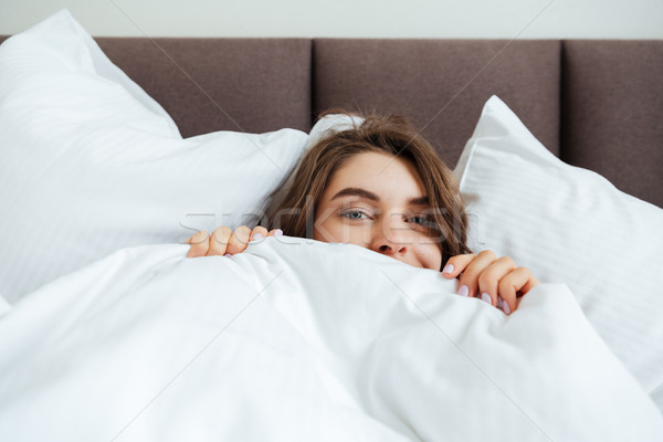 Happy young lady lies in bed at home under a blanket. Stock photo © deandrobot