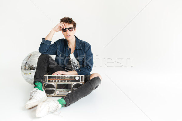 Serious young man with disco ball and boombox. Stock photo © deandrobot
