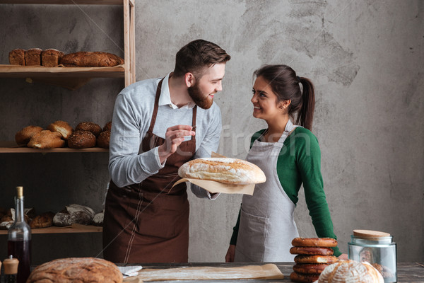 Smiling loving couple bakers standing at bakery holding bread Stock photo © deandrobot