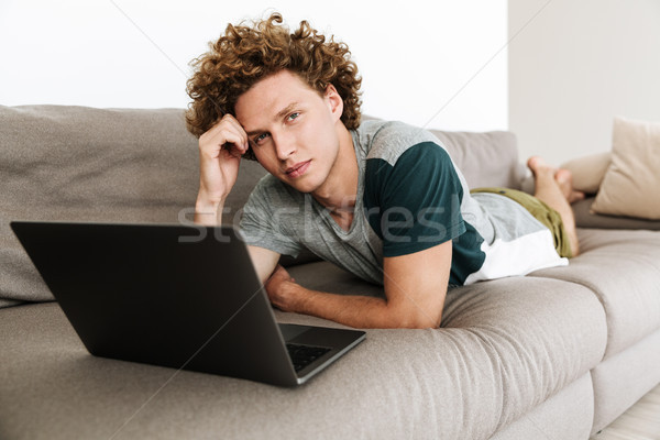 Handsome concentrated man lies on sofa using laptop Stock photo © deandrobot