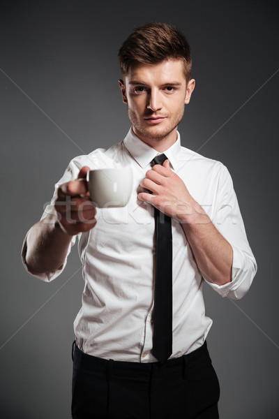 Successful businessman in formalwear holding cup of coffee while standing Stock photo © deandrobot