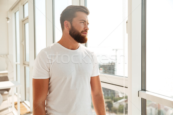Side view of mystery bearded man looking at the window Stock photo © deandrobot