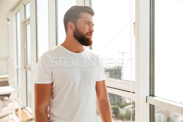 Widok z boku tajemnicy brodaty człowiek patrząc okno Zdjęcia stock © deandrobot