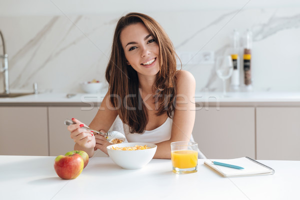 Smiling healthy woman eating corn flakes cereal Stock photo © deandrobot