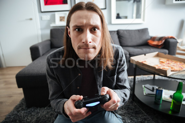 Concentrated man sitting at home indoors play games Stock photo © deandrobot