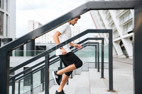 Zijaanzicht jonge mannelijke runner lopen naar boven Stockfoto © deandrobot