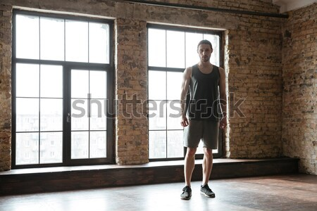 Young confident sportsman warming up at the gym Stock photo © deandrobot